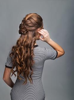 Penteado de cachos ondulados. penteado na mulher de cabelo castanho vermelho com cabelo comprido em fundo cinza. serviços profissionais de cabeleireiro. modelagem do cabelo, confecção de tranças com grampo.