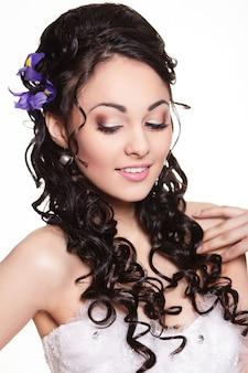Penteado de casamento de beleza com flores brilhantes e maquiagem brilhante