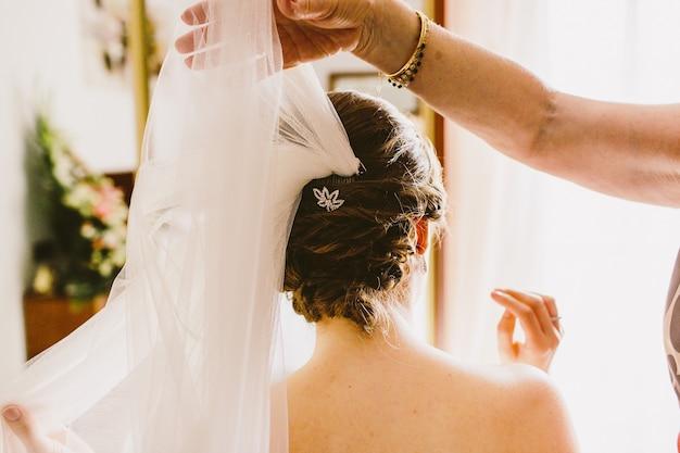 Penteado de uma mulher no dia do casamento, atrás de uma noiva.