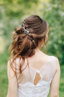 Penteado despenteado na noiva com um pequeno barrete vista por trás