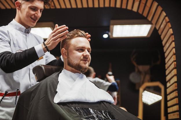 Penteado e corte de cabelo masculino em uma barbearia ou salão de cabeleireiro.