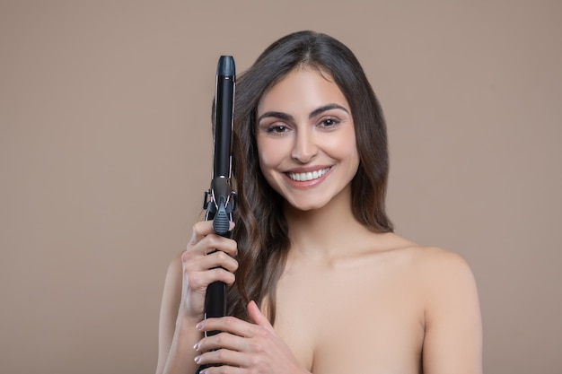 Penteado elegante. linda mulher sorridente de cabelos compridos seminua com modelador de cabelo perto da cabeça em fundo bege