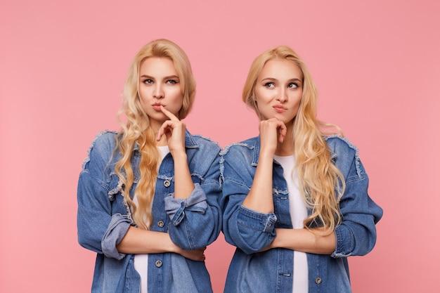 Penteado encaracolado de jovens atraentes e intrigados tocando o rosto com as mãos levantadas e torcendo a boca pensativamente em pé sobre um fundo rosa em casacos jeans