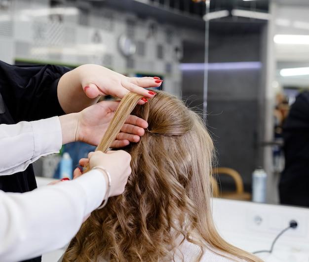 Penteado no centro de treinamento de cabelo para cabeleireiro estilista. cabeleireiro fazendo penteado para mulher loira com cabelo comprido em salão de beleza
