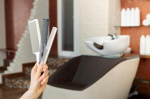 Pentes para cabelo cortado na mão de cabeleireiro feminino contra cadeira de pia de lavagem de cabelo no salão de beleza