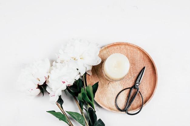 Peônia branca e bandeja de madeira com vela, tesoura no fundo branco. aconchegante, ainda vida, conceito mínimo. vista superior, configuração plana, cópia espaço