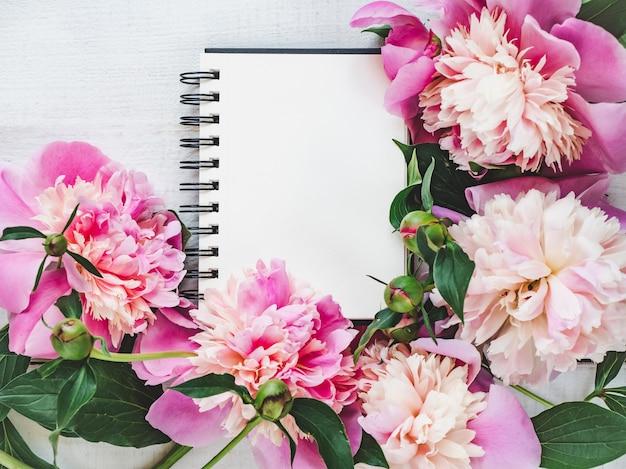 Peônias brilhantes, página de bloco de notas em branco sobre uma mesa de madeira