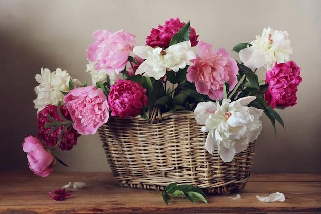 Peônias-de-rosa, vermelhas e brancas em uma cesta na mesa