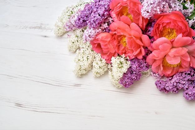 Peônias e flores lilás sobre fundo branco de madeira.