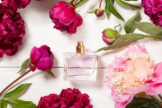 Peônias e perfume em um fundo de madeira. aroma de flores
