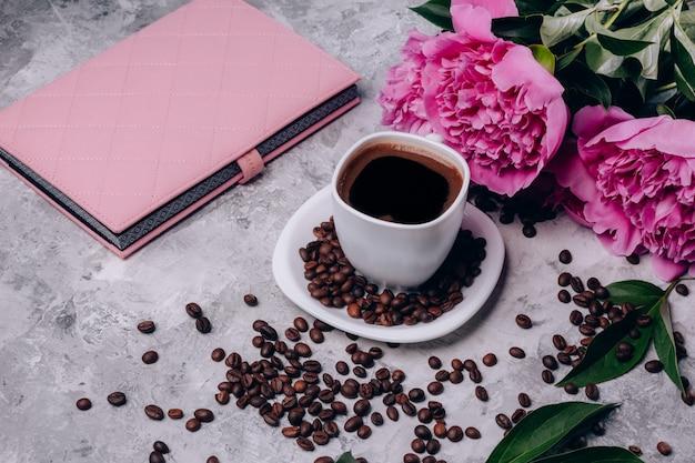 Peônias flores sobre a mesa e uma xícara de café