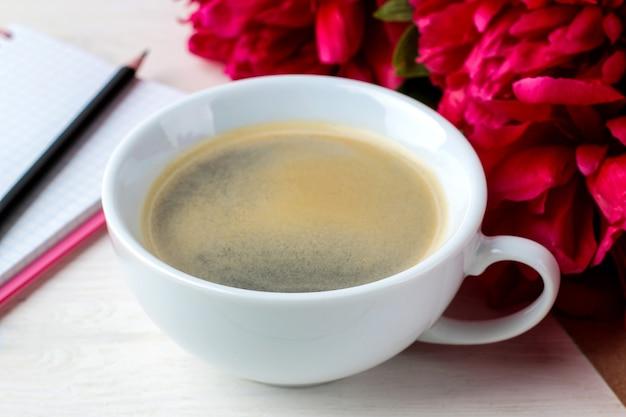 Peônias lindas flores rosa brilhantes e uma xícara de café em um fundo branco de madeira.
