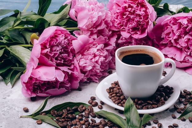 Peônias na mesa uma xícara de café e grãos de café