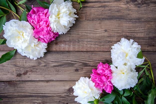 Peônias rosa e brancas sobre fundo de madeira