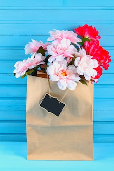 Peônias rosa em um pacote de ofício com um quadro em uma mesa de madeira azul. postal para o feriado.