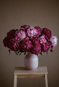 Peônias rosa escuras em um vaso. ainda vida. fundo marrom