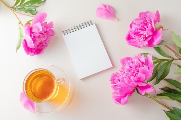 Peônias rosa frescas brilhantes, um notebook com uma página em branco e uma xícara de chá em uma xícara transparente e pires sobre um fundo claro.