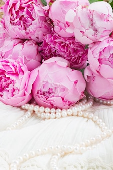 Peônias rosa frescas com pérolas em renda branca