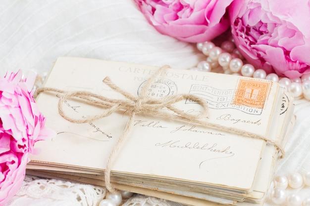 Peônias rosa frescas com pilha de correspondência velha e pérolas