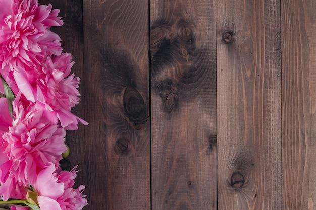 Peônias rosa sobre fundo de madeira