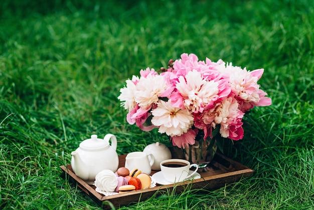 Peônias, um bule de chá e uma xícara de chá em uma bandeja de madeira