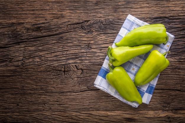 Peper verde. toalha de mesa quadriculada azul de pimenta verde fresca na velha mesa de carvalho. Foto Premium