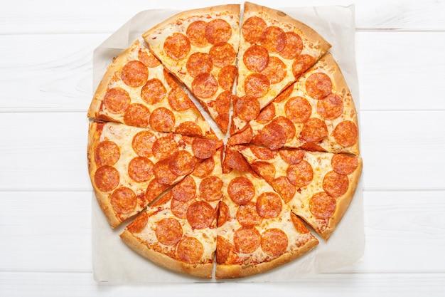 Peperoni da pizza no fundo branco.