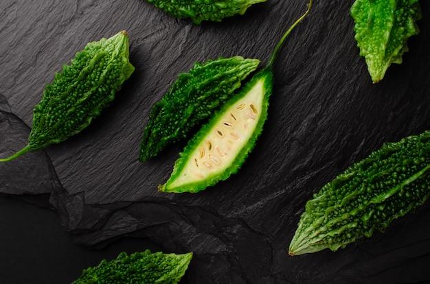 Pepino amargo ou momordica no fundo preto da ardósia. conceito exótico da culinária. configuração plana