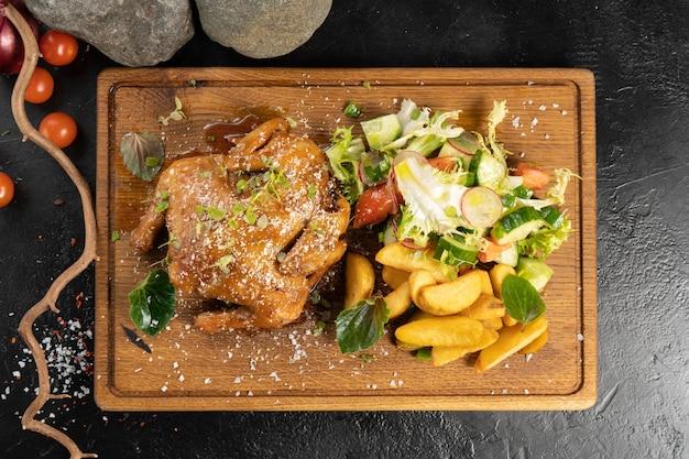 Pepino de frango assado com batatas e legumes frescos em uma tábua de madeira