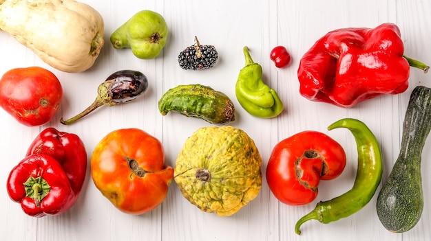 Pepino de vegetais orgânicos feios, pimentão, berinjela, amora, dogwood, abóbora, abobrinha, pêra e tomate na mesa branca, conceito de comida feia, vista superior