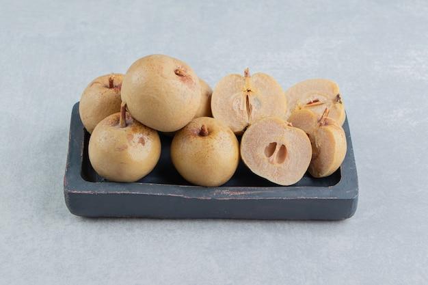 Pepino em conserva e maçãs em placa de madeira na superfície de mármore