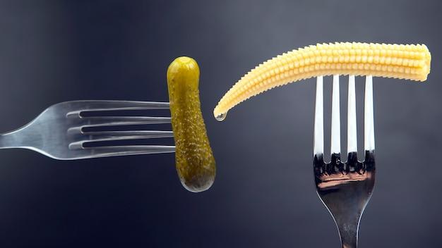 Pepino em conserva e milho em um garfo close-up