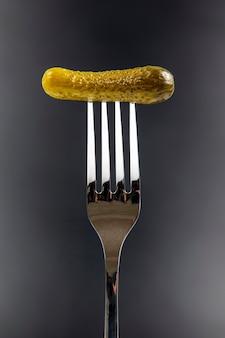 Pepino em conserva em um garfo em um fundo escuro. comida e vegetais