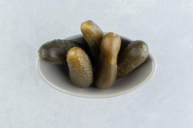Pepino em conserva na tigela, na superfície de mármore
