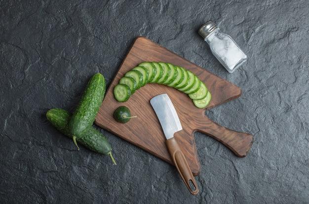 Pepino fatiado ou inteiro na placa de madeira com sal e faca. foto de alta qualidade