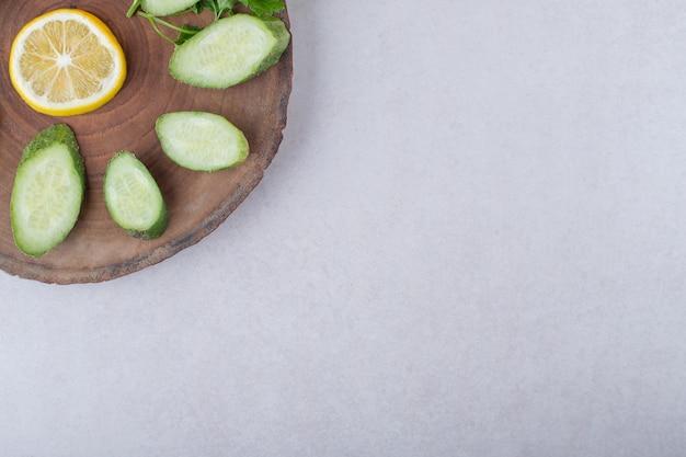 Pepino fresco fatiado, limão e salsa em uma placa, no mármore.