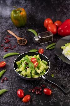 Pepino frito com tomate e feijão vermelho em uma frigideira.