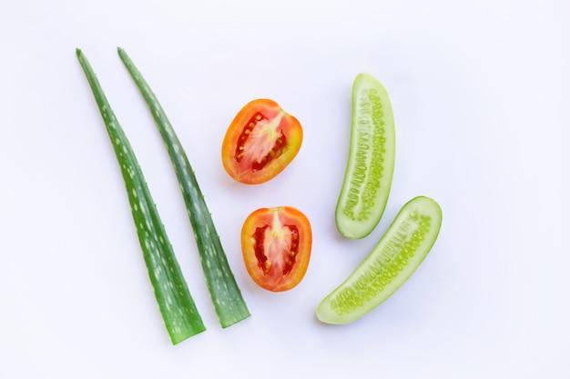 Pepino, tomate, aloés vera, ingredientes naturais para cuidados com a pele caseiros no branco.