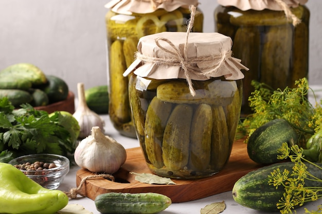 Pepinos com alho, pimenta e endro em potes de vidro em fundo cinza claro com vegetais ao redor