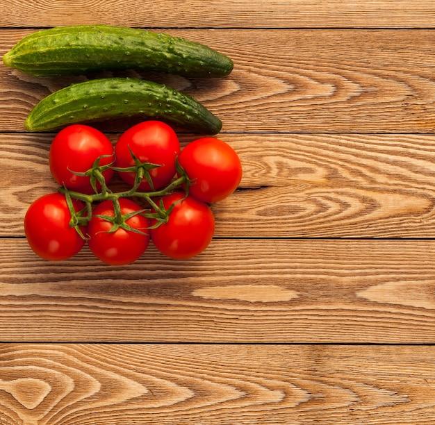 Pepinos e tomates em uma madeira Foto Premium