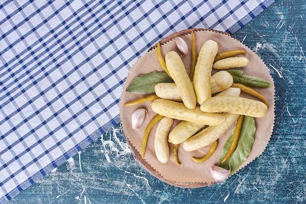 Pepinos em conserva, alho, pimentão e folhas na placa de madeira com toalha de mesa.