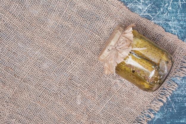 Pepinos em conserva caseiros em frasco de vidro em azul com toalha de mesa de lã.