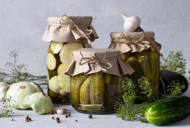 Pepinos em conserva caseiros, patissons e abobrinha em potes de vidro em fundo cinza claro com ingredientes frescos, closeup.
