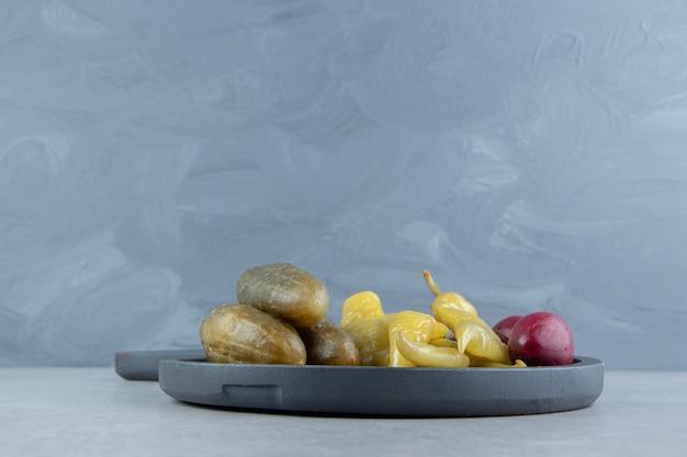 Pepinos em conserva e pimenta no quadro escuro.