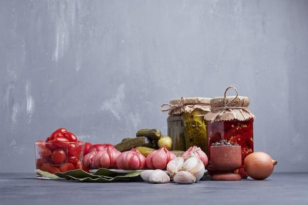 Pepinos em conserva e pimentão vermelho em frasco de vidro com folhas, alho, cebola e pimentão.