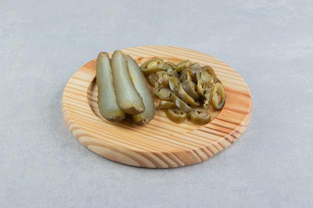 Pepinos em conserva e pimentas na placa de madeira.