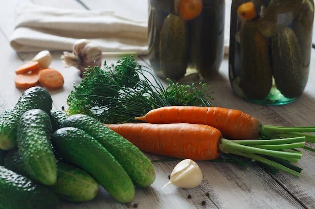 Pepinos em conserva em uma jarra e um conjunto de ingredientes cenouras, endro verde, pimenta da jamaica em uma mesa de madeira branca
