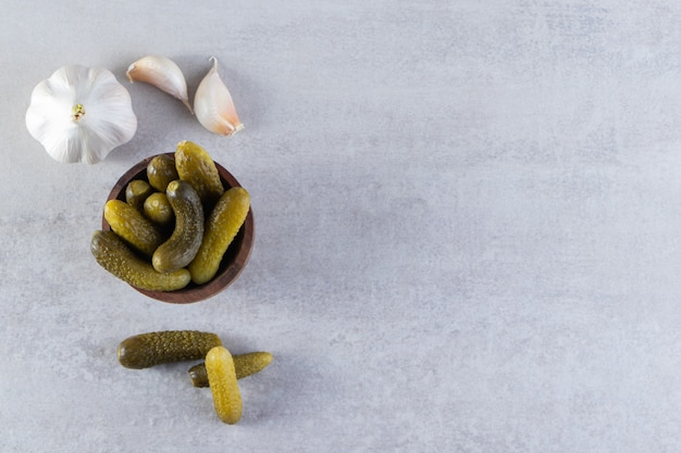 Pepinos em conserva marinados deliciosos colocados na mesa de pedra.