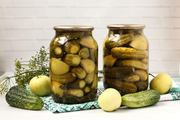 Pepinos em vinagre com maçãs em frascos são dispostos em um fundo branco