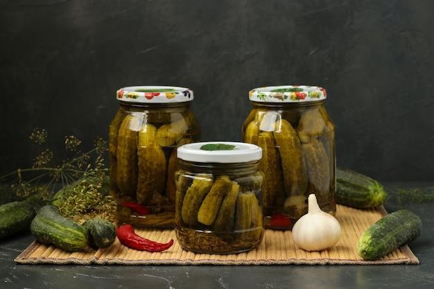 Pepinos em vinagre em vasos estão localizados sobre uma mesa, sobre um fundo escuro.